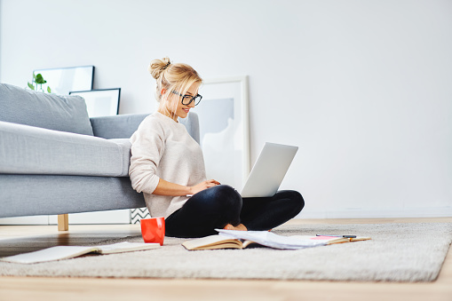 女學生坐在她的公寓地板上 筆記本電腦和筆記學習 照片檔及更多 20多歲 照片