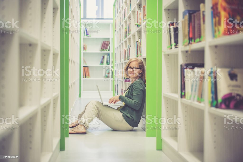 Female student sitting on library floor at college campus with laptop computer stock photo