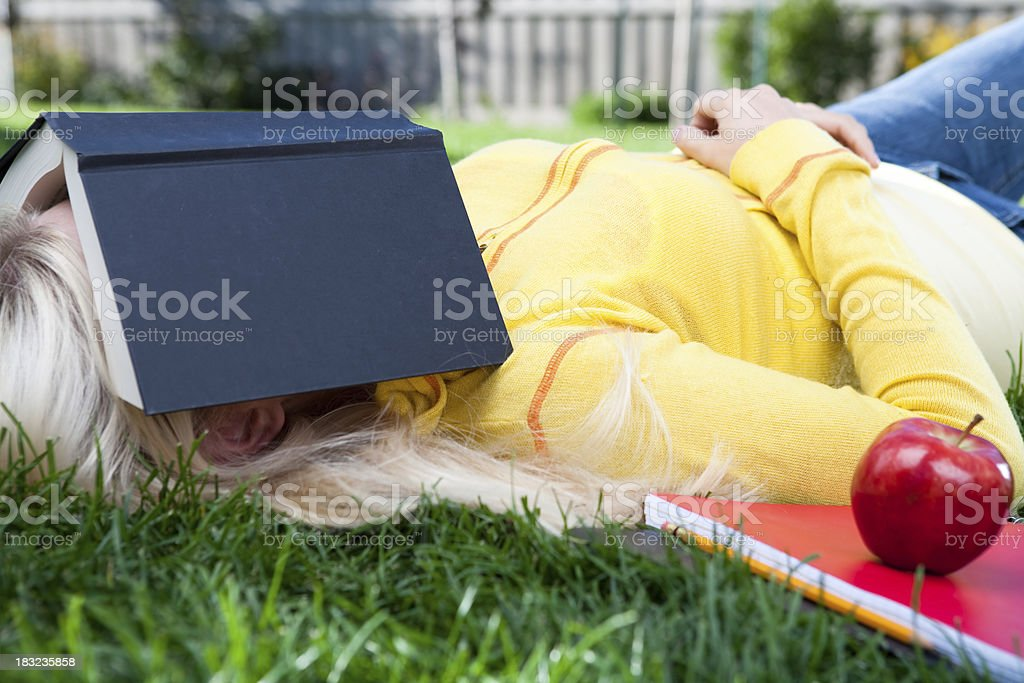 Female student sleeping on grass royalty-free stock photo