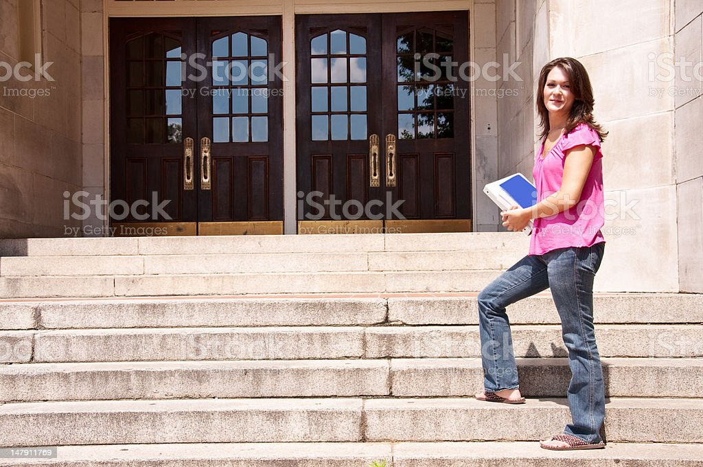 Female Student Standing at School Door with Textbooks royalty-free stock photo