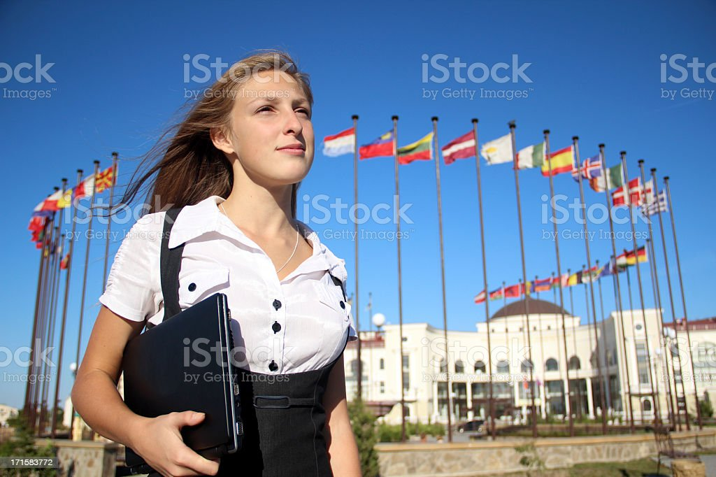 Female student standing in front of international flags royalty-free stock photo