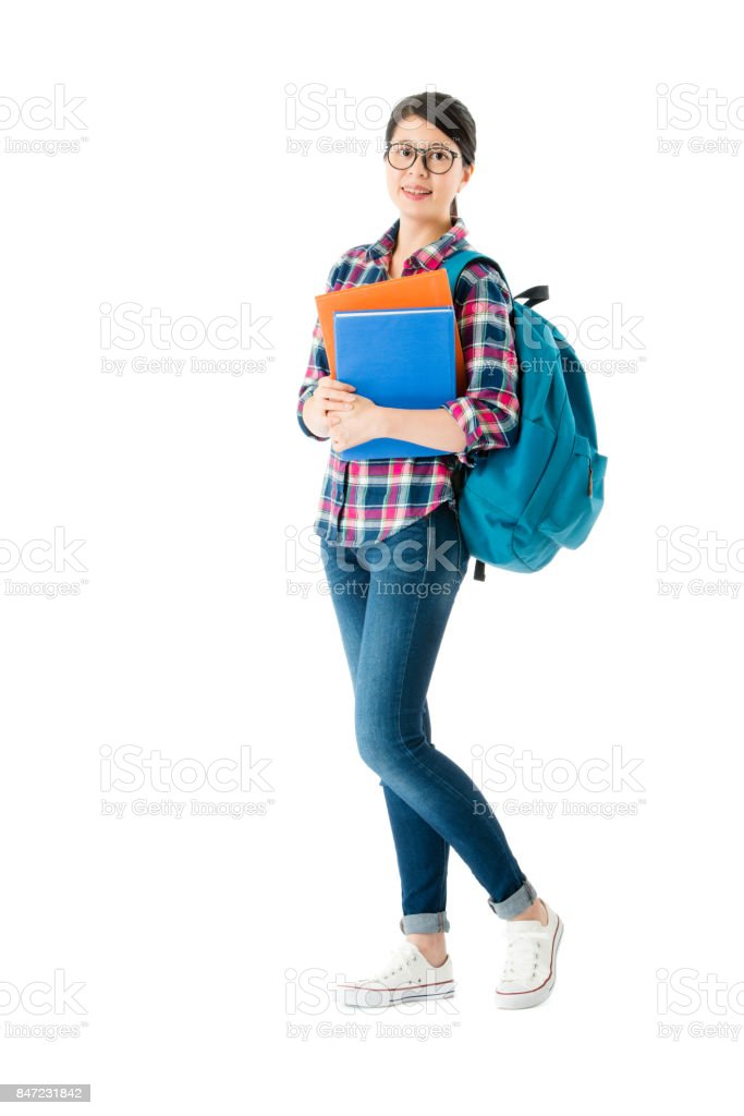 female student standing on white wall background stock photo