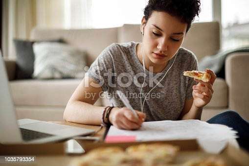 Female student studying and listening to music at home