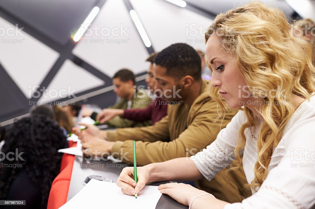 Female student taking notes in a university lecture theatre stock photo