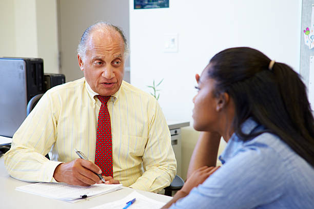 female student talking to high school counselor - school counselor stock photos and pictures
