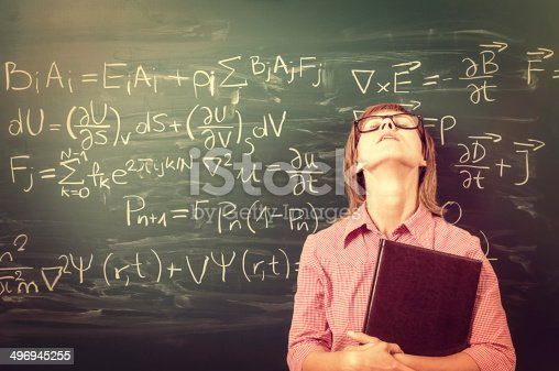 Close-up on female student or teacher in horn rimmed glasses standing against green chalkboard. She is tired of learning, teaching, school and exams. Retro style. Heavy processing for retro look, slight vignette added.
