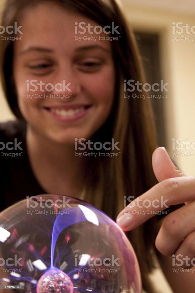 Female student touching a plasma ball. royalty-free stock photo