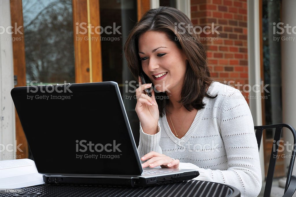 Female Student Using Computer and Cell Phone royalty-free stock photo