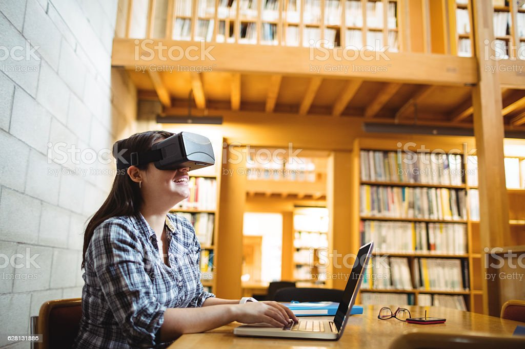 Female student using laptop and virtual reality headset in library - foto de acervo
