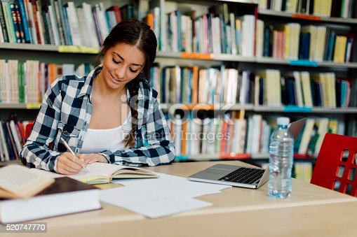 istock Female student using laptop for taking notes to study. 520747770