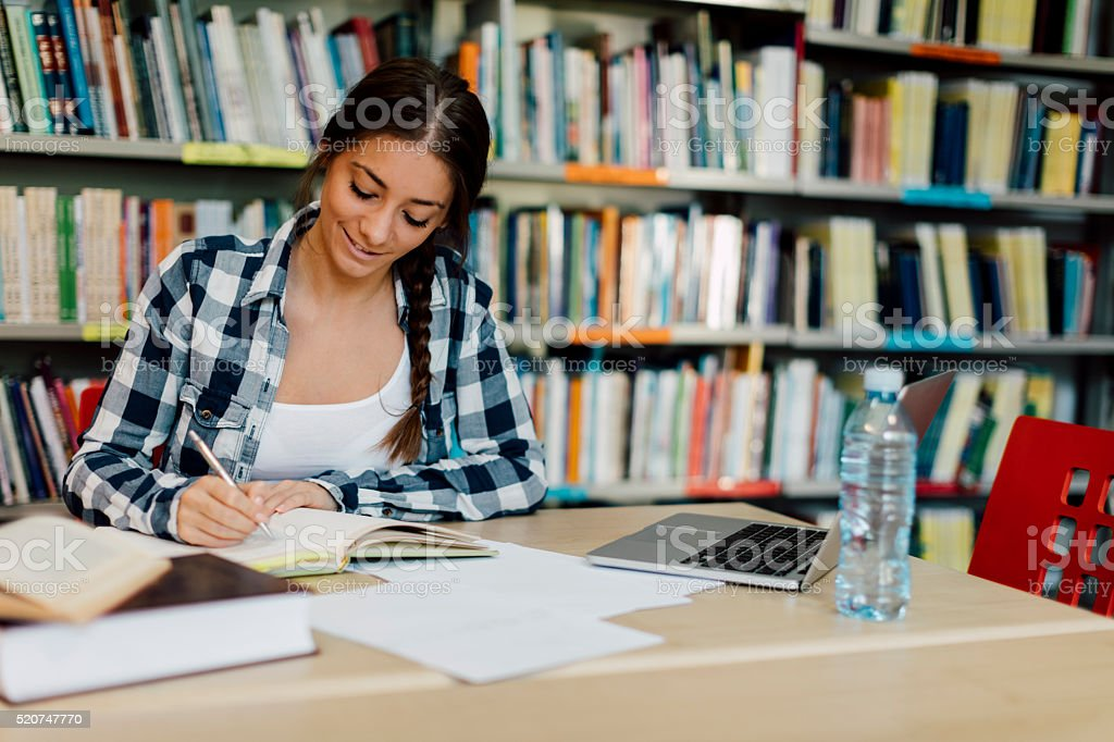 Female student using laptop for taking notes to study. stock photo