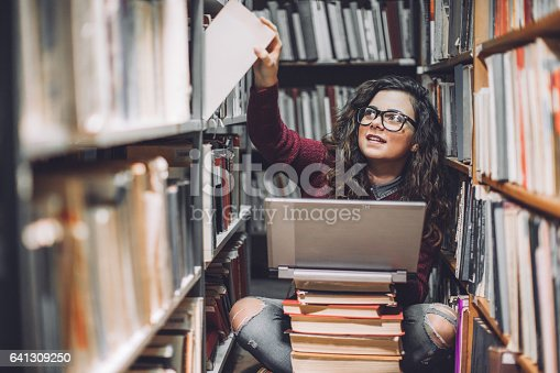 istock Female student using laptop for taking notes to study 641309250