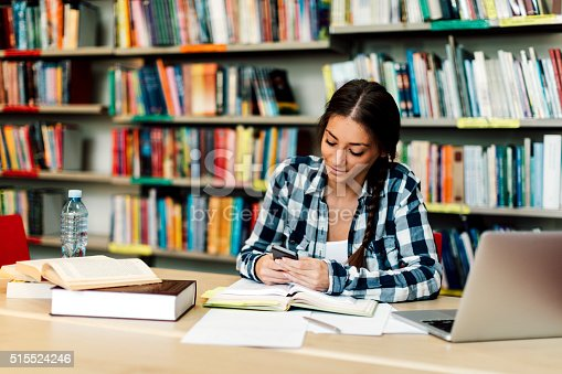 istock Female student using smart phone in library 515524246