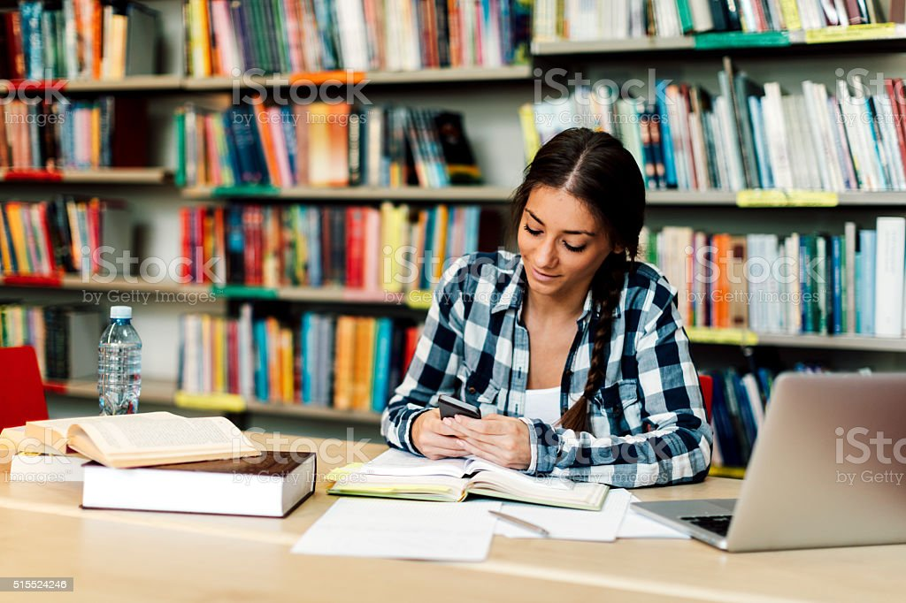 Female student using smart phone in library stock photo