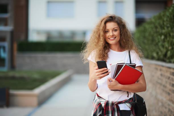 Female student using smart phone. stock photo