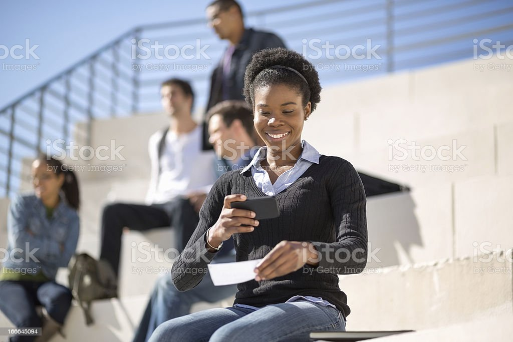 Female Student Using Smart Phone To Deposit Check stock photo