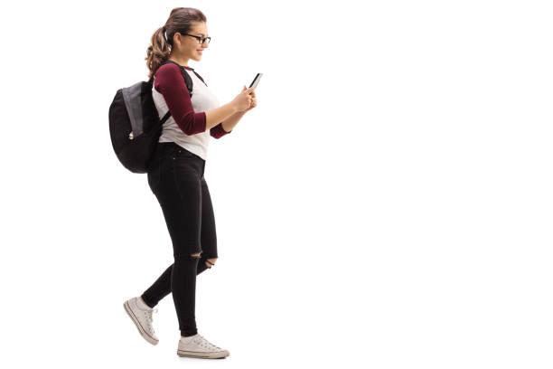 female student walking and looking at mobile phone - damenrucksack stock-fotos und bilder