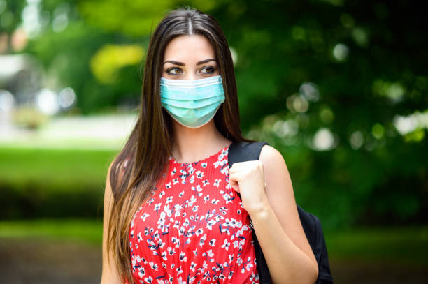 Female student walking outdoor in the park and wearing a mask to protect herself from coronavirus stock photo