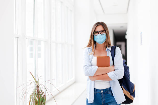 Female student wearing mask indoors. Exams in high school. Young woman in empty university. stock photo