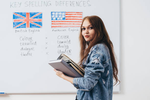 Female student with books in classroom English language school. stock photo
