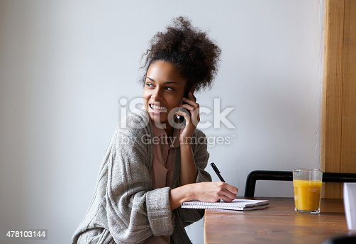 istock Female student working at home and talking on mobile phone 478103144