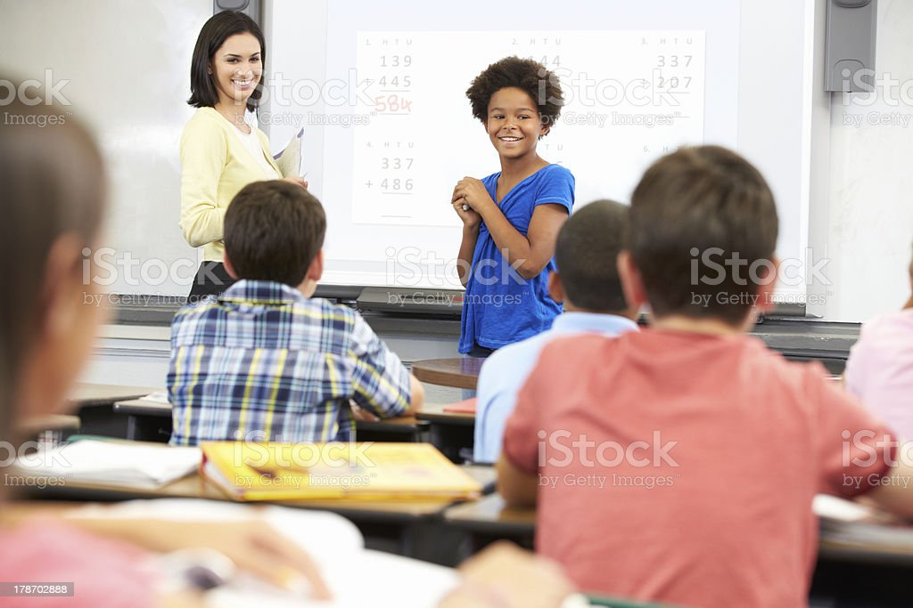 Female Student Writing Answer On Whiteboard stock photo