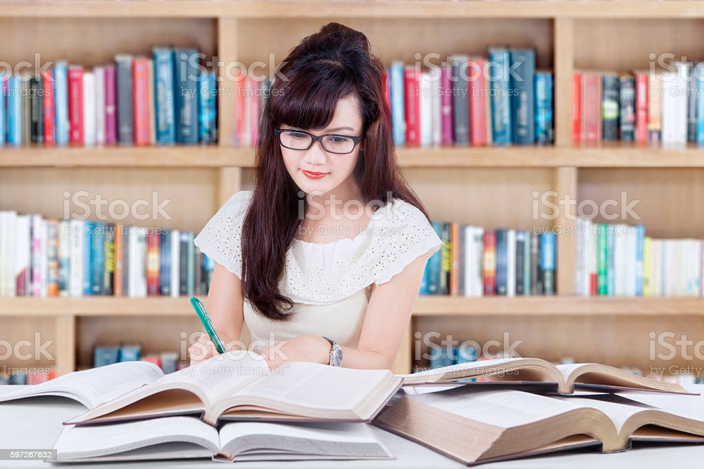 Female student writing in the library royalty-free stock photo