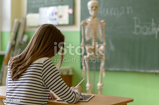 istock Female student writing notes using digital tablet in biology class. Generation Z Education concept. 944014630