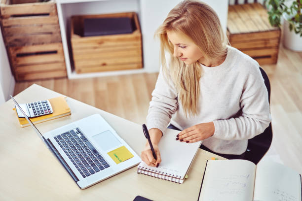 Schreiben von Notizen während mit Laptop Studium zu Hause Studentin – Foto