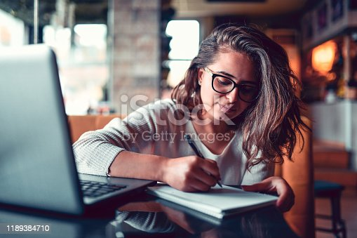 Female Student Writing Paper In Coffee Bar