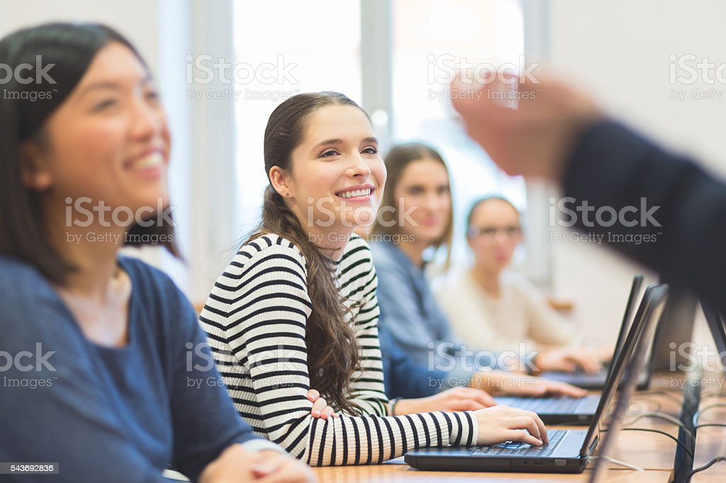 Female students coding Multi ethnic group of happy female students coding on laptops in a computer lab, listening to their teacher. Achievement Stock Photo