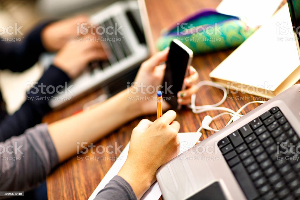 Female students hands working with laptop and cellphone in classrroom stock photo