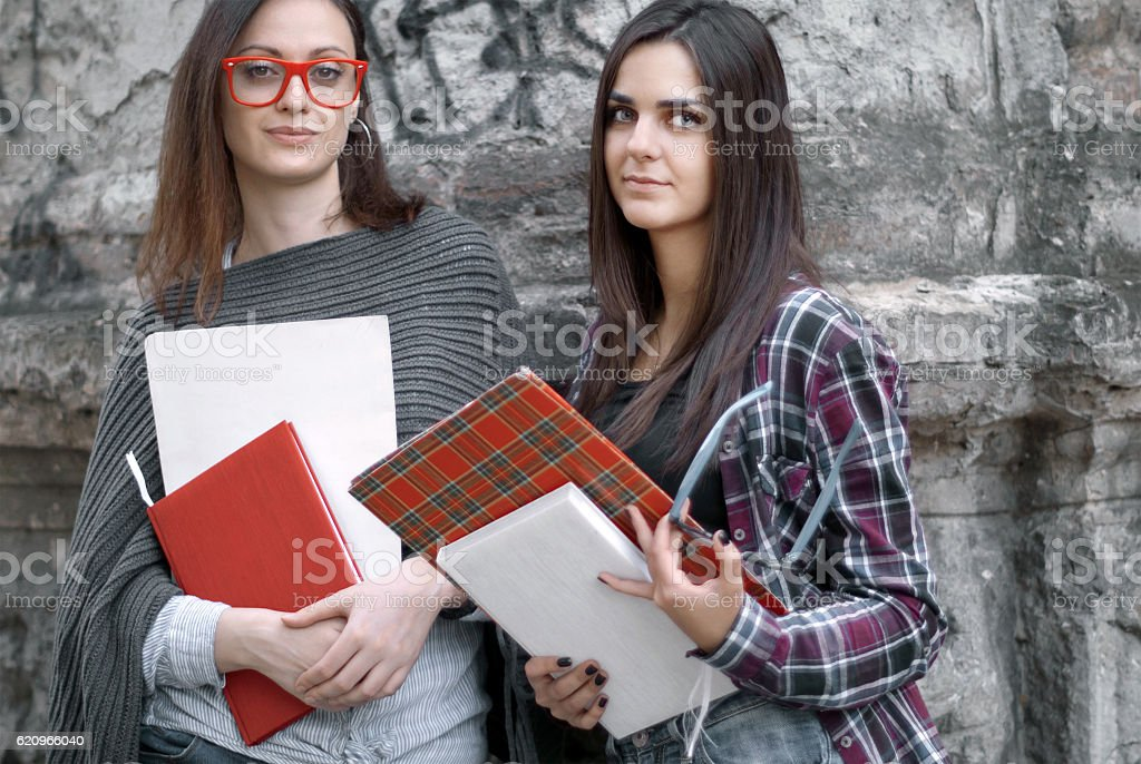 Female students holding school books outside campus classroom stock photo