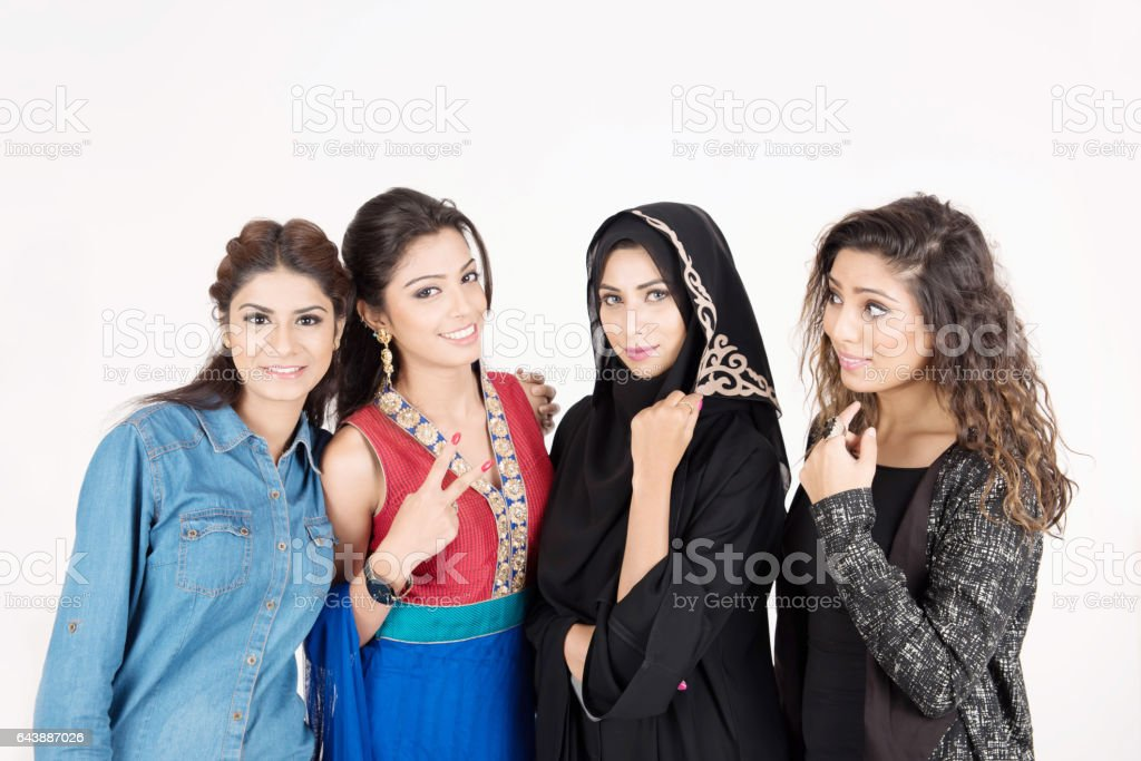 Female students in traditional dresses from different cultures stock photo