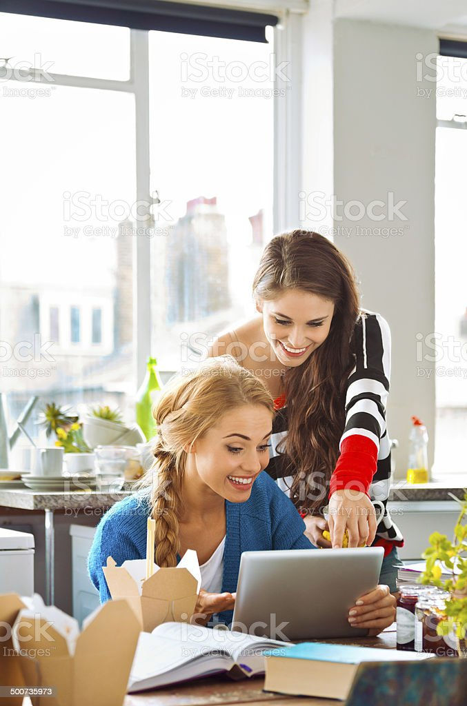 Female students learning at home Two female friends using a digital tablet together at home, sitting in a kitchen at the messy table. 20-24 Years Stock Photo