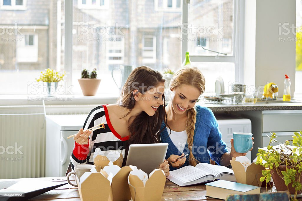 Female students learning at home Two friends sitting at the kitchen table at home and learning together. 20-24 Years Stock Photo