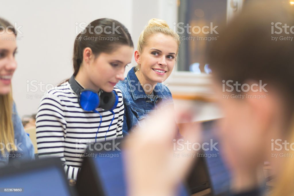 Female students learning computer programming Group of female students coding on laptops in a computer lab. Adult Stock Photo