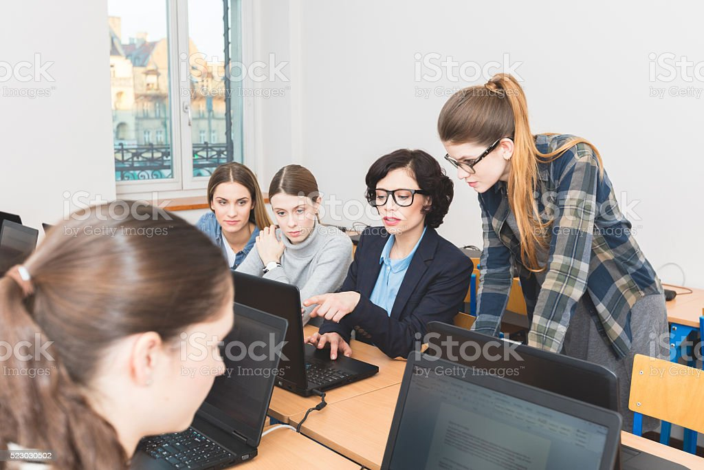 Female students learning computer programming Group of female students coding on laptops in a computer lab. Teacher showing something on computer screen. Adult Stock Photo