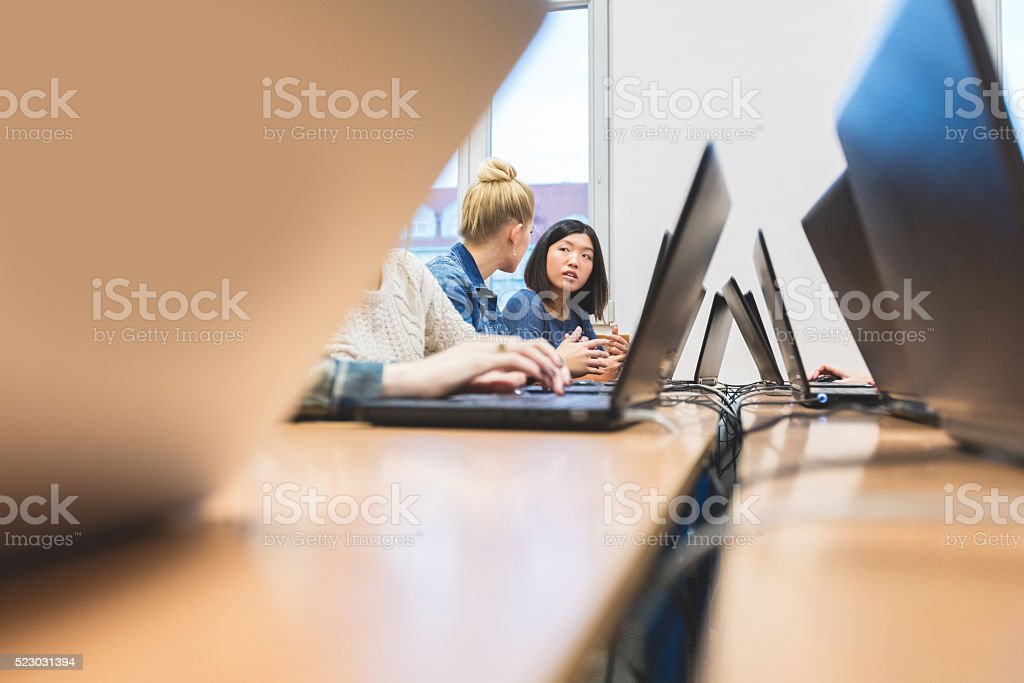 Female students learning computer programming Multi ethnic female students coding on laptops in a computer lab. Asian girl talking with blonde. Adult Stock Photo