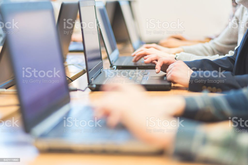 Female students learning computer programming Group of female students coding on laptops in a computer lab. Close up of hands, unrecognizable people. Achievement Stock Photo
