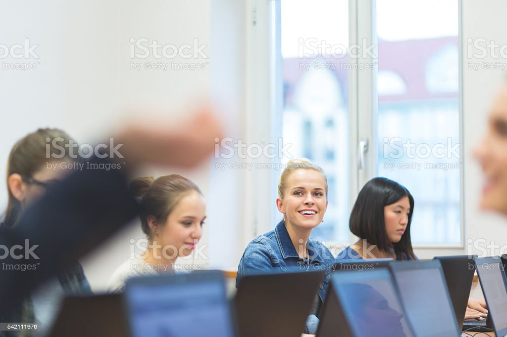 Female students learning computer programming Group of female students coding on laptops in a computer lab.  Achievement Stock Photo
