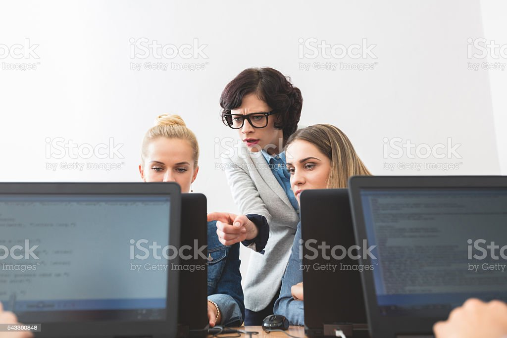 Female students learning computer programming Young women coding on laptops in a computer lab. Teacher showing something on computer screen. Achievement Stock Photo