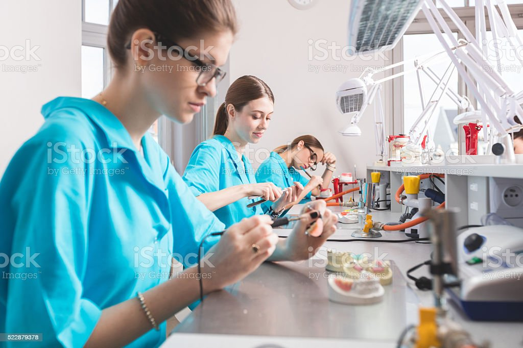 Female students learning prosthetic dentistry stock photo