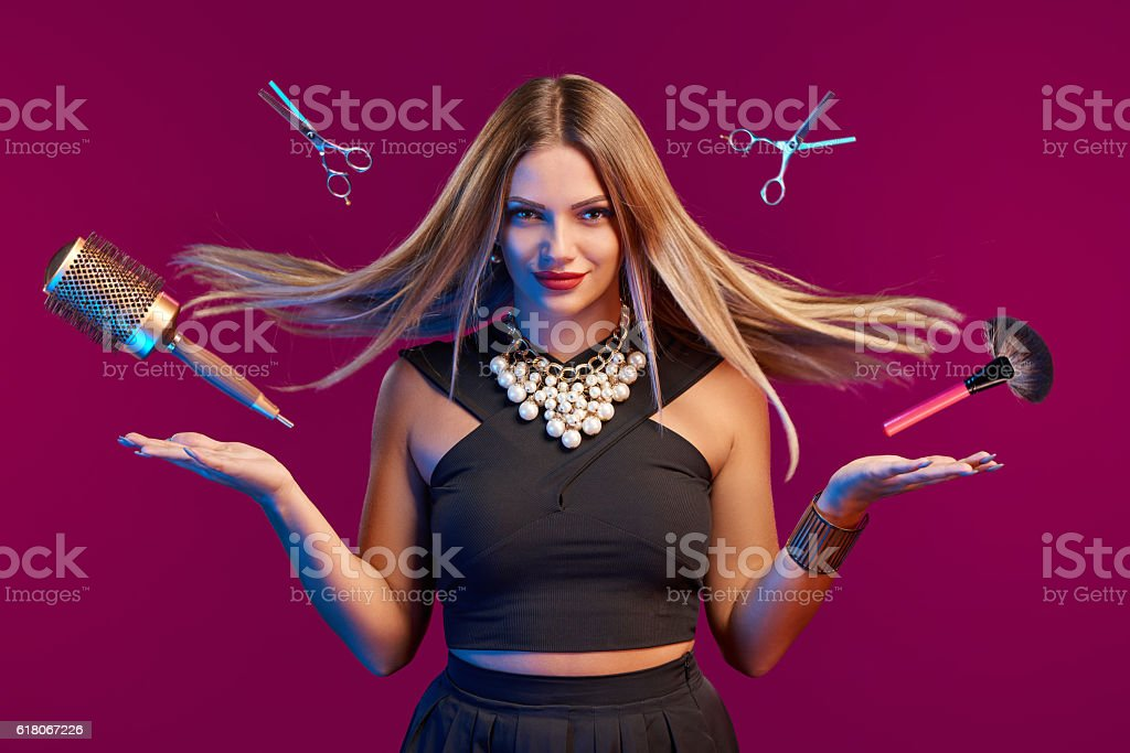 Female stylist with hair flying holding makeup brushes – Foto