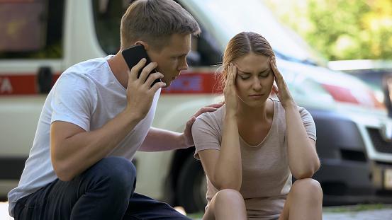 istock Female suffering headache, not indifferent man calling ambulance, first aid 1131889213