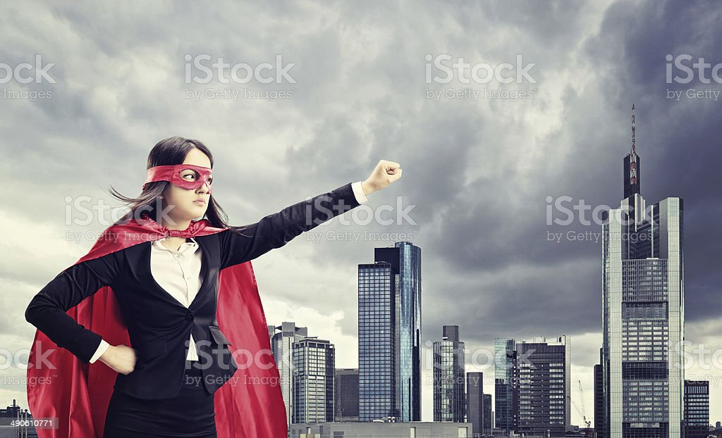 Female superhero standing in front of a city stock photo