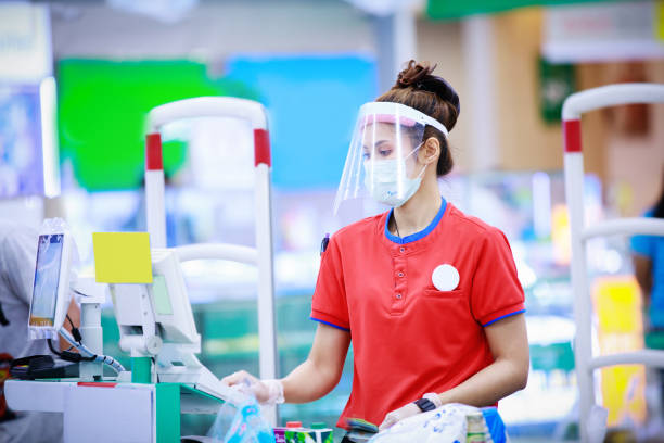 female supermarket cashier in medical protective mask and face shield working at supermarket - servizi essenziali foto e immagini stock
