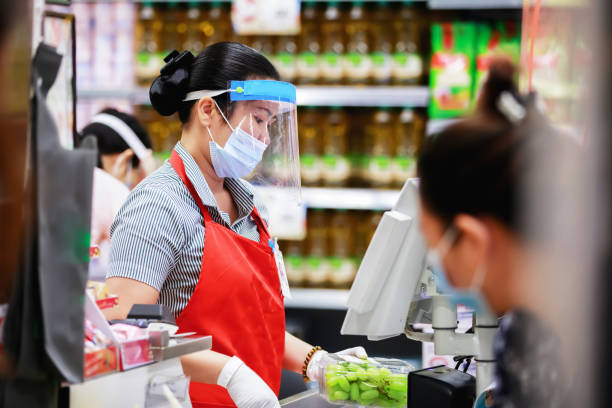 female supermarket cashier in medical protective mask working at supermarket - servizi essenziali foto e immagini stock