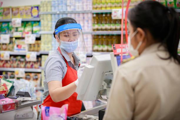 cajera de supermercado femenino en máscara de protección médica que trabaja en el supermercado - foto de stock