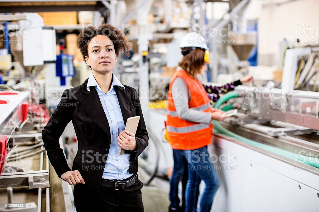 Female supervisor in the factory holding the tablet stock photo